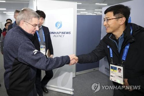 聯合ニュースのブースを訪れたIOCのバッハ会長(左)=12日、平昌(聯合ニュース)