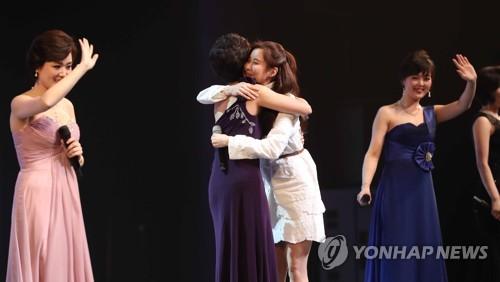 ソウルでの公演で歌った後、芸術団員と抱き合う韓国ガールズグループ・少女時代のソヒョンさん(右)=11日、ソウル(聯合ニュース)