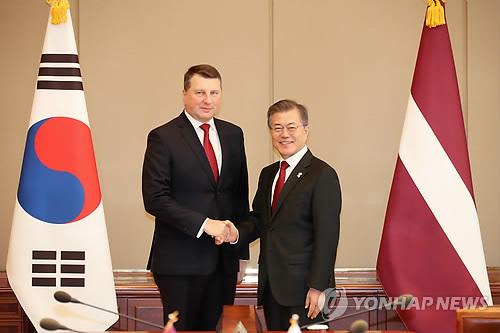 首脳会談で握手を交わす文大統領(右)とベーヨニス大統領=13日、ソウル(聯合ニュース)