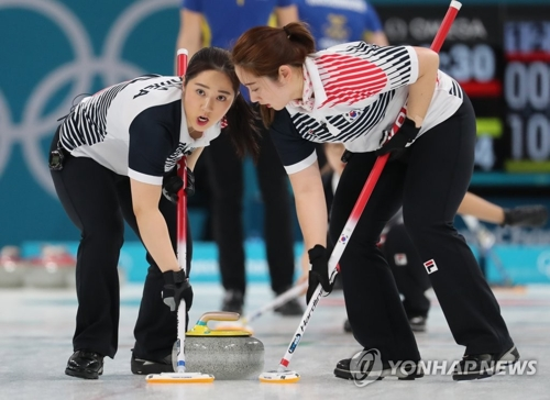 ストーンをスイープする韓国代表=25日、江陵(聯合ニュース)