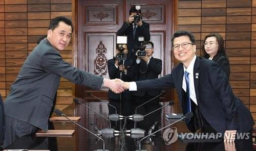 握手を交わす韓国統一部の李柱泰(イ・ジュテ)交流協力局長(右)と北朝鮮・祖国平和統一委員会の黄忠誠(ファン・チュンソン)部長(統一部提供)=27日、板門店(聯合ニュース)