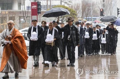遺骨を抱えて歩く日帝強制徴用犠牲者遺骸奉還委員会の関係者=28日、ソウル(聯合ニュース)