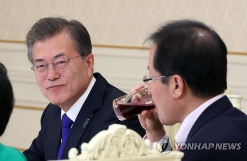 与野党代表との会合で笑みを浮かべる文大統領=7日、ソウル(聯合ニュース)