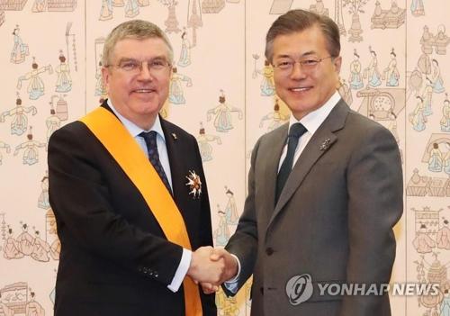 バッハ会長にスポーツ勲章最高位の青龍章を授与した文大統領(右)=8日、ソウル(聯合ニュース)