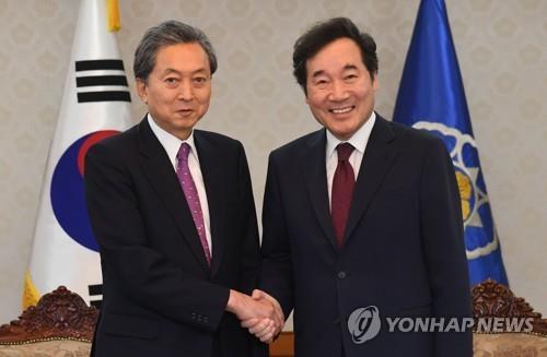鳩山氏と握手する李首相(右)=8日、ソウル(聯合ニュース)