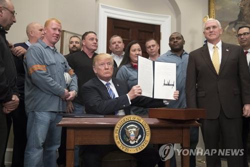自らが署名した輸入制限の文書を掲げるトランプ氏=8日、ワシントン(EPA=聯合ニュース)