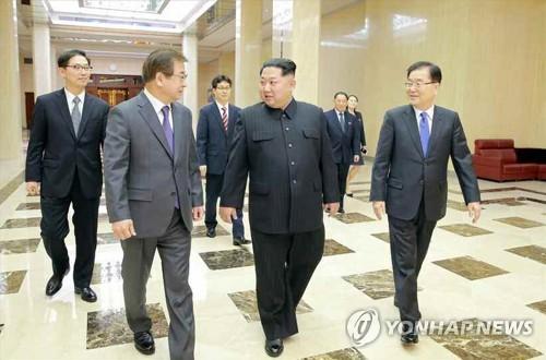6日、平壌で金委員長(中央)と会話する徐氏(手前左)=(労働新聞=聯合ニュース)