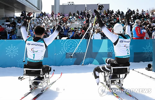 競技後、観客にあいさつするマ・ユチョル(右)とキム・ジョンヒョン=11日、平昌(聯合ニュース)