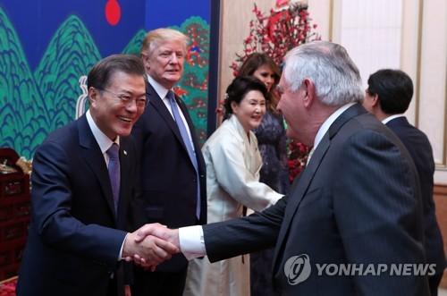 昨年11月7日、トランプ大統領の訪韓に合わせて青瓦台で開かれた夕食会で握手を交わす文大統領(左)とティラーソン氏=(聯合ニュース)