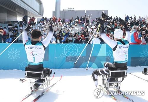 競技を終えて観客の声援に応えるマ・ユチョル(右)とキム・ジョンヒョン=11日、平昌(聯合ニュース)