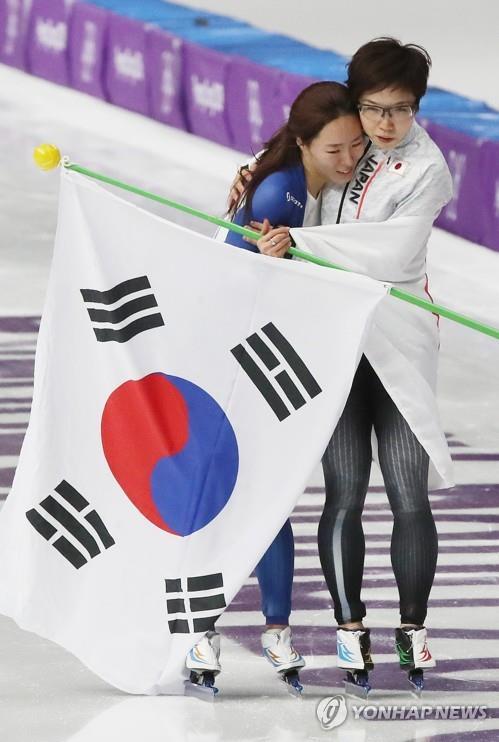 平昌冬季五輪のスピードスケート女子500メートルのレース後に健闘をたたえ合う李選手(左)と小平選手=(聯合ニュース)