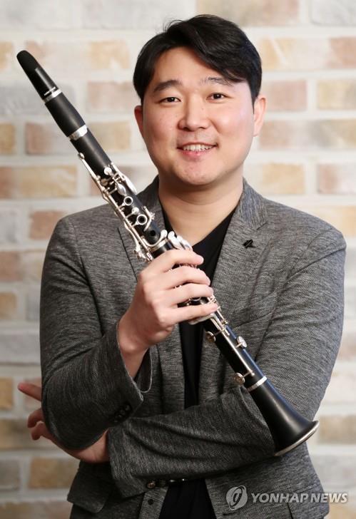 インタビュー前の写真撮影に応じたクラリネット奏者のチョ・ソンホ氏=16日、ソウル(聯合ニュース)