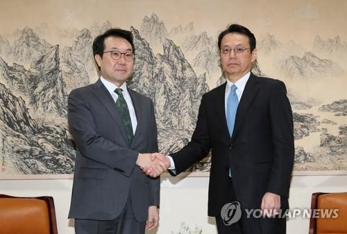 握手を交わす李氏(左)と金杉氏=23日、ソウル(聯合ニュース)