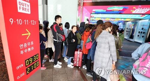 免税店の開店を待つ外国人観光客=24日、ソウル(聯合ニュース)