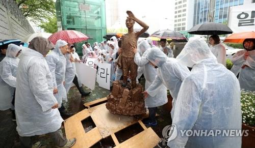 市民団体が行った総領事館前に像の模型を設置するパフォーマンスの様子=24日、釜山(聯合ニュース)
