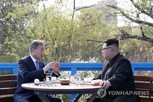 午後の会談前、「徒歩の橋」で話し合う文大統領(左)と金委員長=27日、板門店(聯合ニュース)