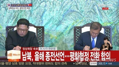 「板門店宣言」に署名する文大統領(右)と金委員長(聯合ニュースTV提供)=(聯合ニュース)