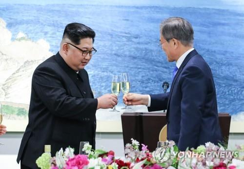 歓迎夕食会で乾杯する文大統領(右)と金委員長=27日、板門店(聯合ニュース)