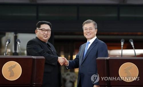 板門店宣言を発表し、握手する文大統領(右)と金委員長=27日、板門店(聯合ニュース)