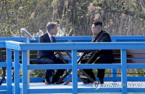 橋の上で話し込む文大統領(左)と金委員長=27日、板門店(聯合ニュース)