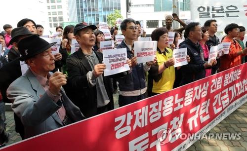 日本総領事館前で会見を行う市民団体のメンバーら=30日、釜山(聯合ニュース)