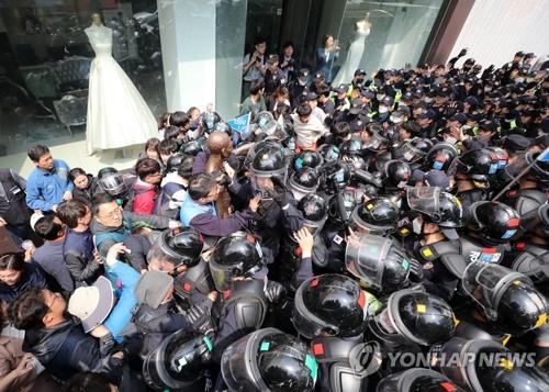 総領事館前に像を設置しようとして、警察ともみ合う団体のメンバー=1日、釜山(聯合ニュース)