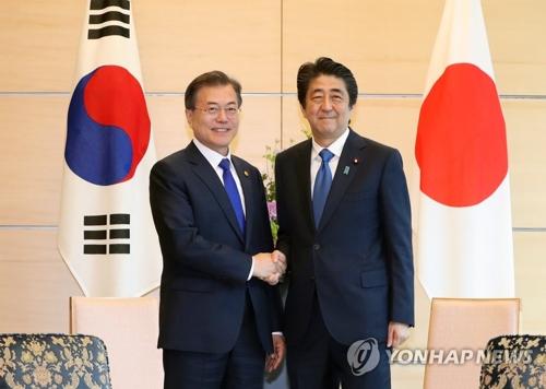 会談前に握手する文大統領と安倍首相=9日、東京(聯合ニュース)