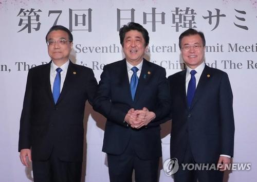 韓国の文在寅(ムン・ジェイン)大統領(右)と安倍晋三首相(中央)、中国の李克強首相が東京・迎賓館で首脳会談を行う前、手を取り合いながら記念撮影を行った=9日、東京(聯合ニュース)