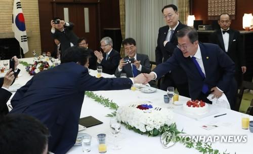 安倍首相(左)からケーキを贈られ、笑顔を浮かべる文大統領=9日、東京(聯合ニュース)