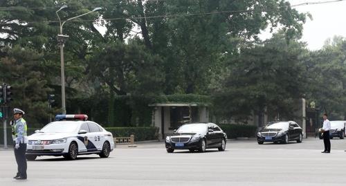 釣魚台迎賓館から出てきた北朝鮮高官一行を乗せているとみられる車両の列=14日、北京(聯合ニュース)