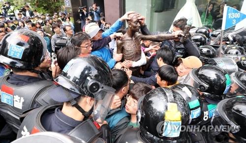 5月1日、総領事館付近でもみ合う市民団体メンバーと警官隊=(聯合ニュース)