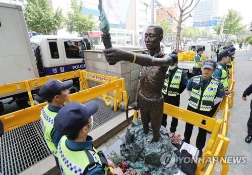 像を取り囲んで警戒を続ける警察=30日、釜山(聯合ニュース)