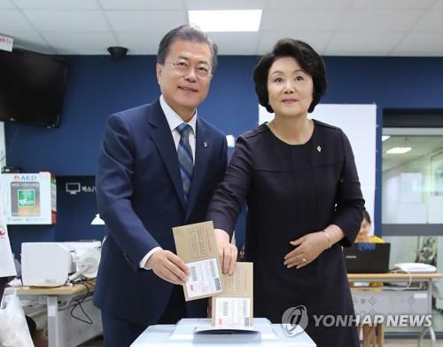 大統領府付近の期日前投票所で投票する文大統領夫妻=8日、ソウル(聯合ニュース)