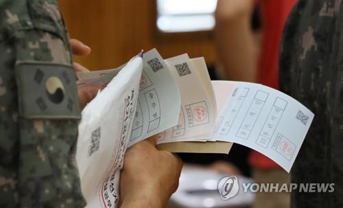 ソウル鍾路区の投票所で投票用紙を確認する有権者=8日、ソウル(聯合ニュース)