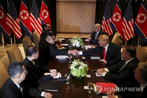 拡大会合で握手する金委員長(左)とトランプ大統領=(ロイター=聯合ニュース)