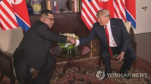 会談で握手を交わす金委員長(左)とトランプ大統領=(聯合ニュースTV)