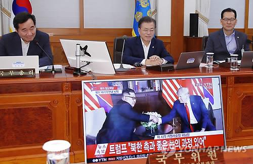 閣議で朝米会談のテレビ中継を視聴する文大統領(中央)=12日、ソウル(聯合ニュース)