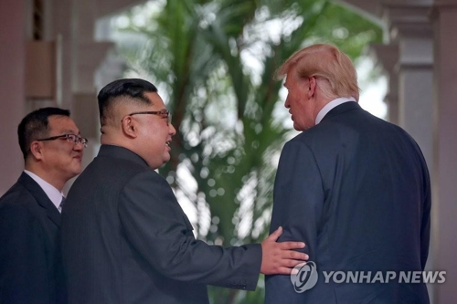 トランプ氏(右)の腕に手を添える金委員長(シンガポール政府提供)=(聯合ニュース)
