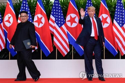 合意文書に署名した金正恩委員長(左)とトランプ大統領=12日、シンガポール(AFP=聯合ニュース)