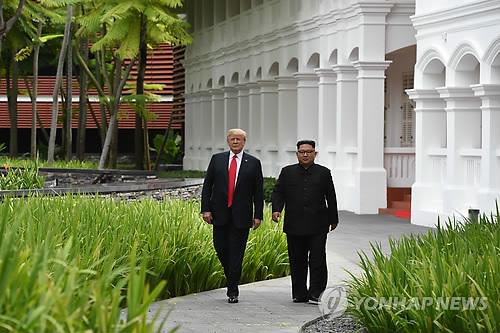 昼食会後、ホテルで散歩する金委員長(右)とトランプ大統領=12日、シンガポール(AFP=聯合ニュース)