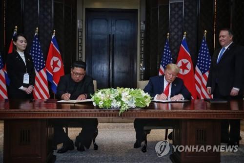 合意文書に署名する朝米首脳=12日、シンガポール(聯合ニュース)