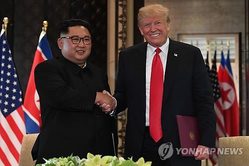 首脳会談を終えたトランプ大統領(右)と金委員長=(AFP=聯合ニュース)