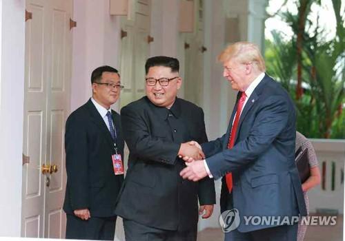 トランプ大統領(右)と笑顔で握手する金委員長=(労働新聞=聯合ニュース)