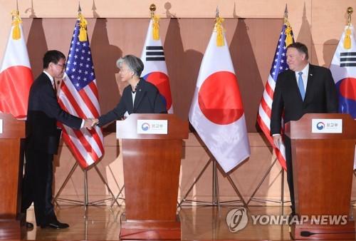 3カ国外相の共同記者会見で握手を交わす康氏(中央)と河野氏=14日、ソウル(聯合ニュース)