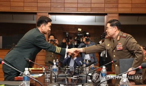 会談の後、共同報道文を交換する韓国側の代表(左)と北朝鮮の代表(韓国国防部提供)=14日、ソウル(聯合ニュース)