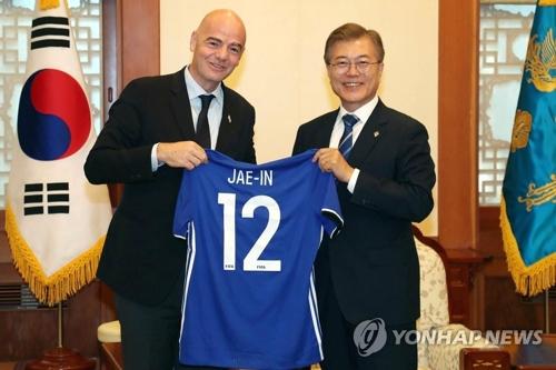 昨年6月、文大統領(右)は国際サッカー連盟(FIFA)のインファンティノ会長から自身の名前入りユニホームを贈られた(資料写真)=(聯合ニュース)