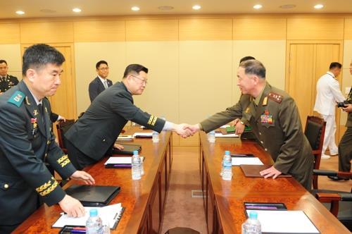 実務協議に出席した国防部のチョ・ヨングン北朝鮮政策課長(左)と北朝鮮のオム・チャンナム大佐(国防部提供)=25日、ソウル(聯合ニュース)