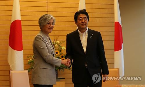 握手を交わす康長官(左)と安倍首相=8日、東京(聯合ニュース)