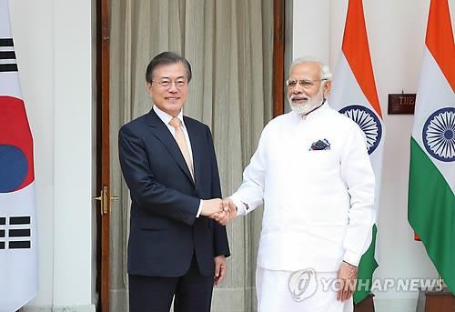 首脳会談で握手を交わす文大統領(左)とモディ首相=10日、ニューデリー(聯合ニュース)