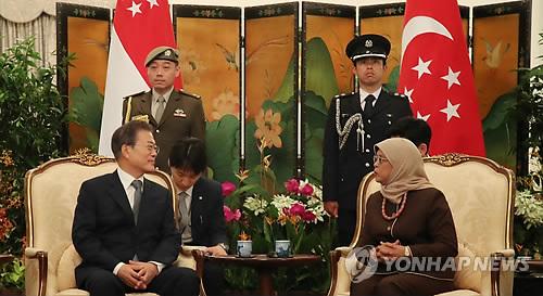 会談する文大統領(左)とハリマ大統領=12日、シンガポール(聯合ニュース)